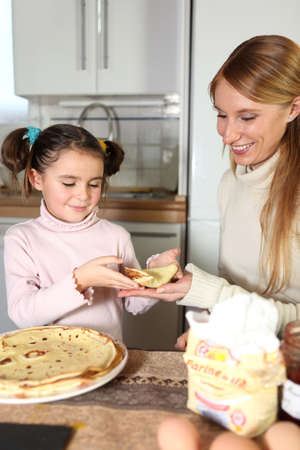 Mother and daughter eating pancakes photo