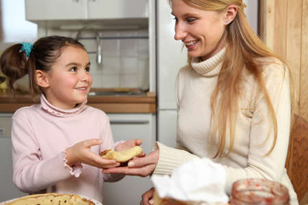 kindness: Little girl giving her mother a crepe Stock Photo
