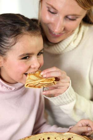 soulfulness: Girl and mom eating pancakes Stock Photo