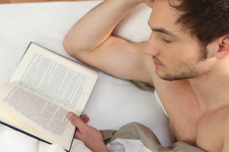 Young man reading in bed photo