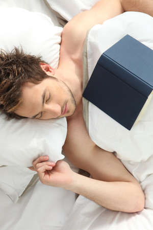 Young man who fell asleep reading a book with a blank hardcover photo