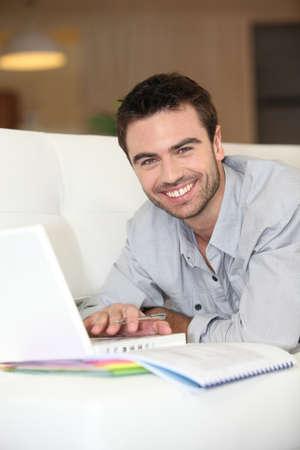 Man lying on sofa with computer photo