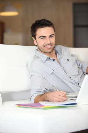 outworking: Smiling man on sofa Stock Photo