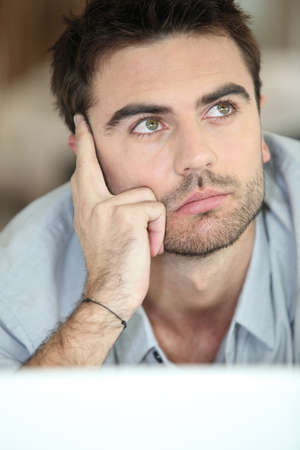 closely cropped: Musing young man looking upwards Stock Photo