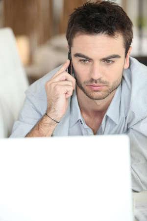 beau jeune homme: Homme sérieux cherche à ordinateur portable Banque d'images