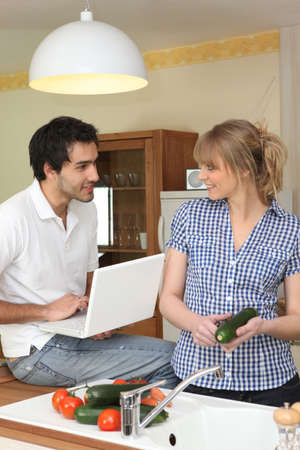 Couple in kitchen with computer photo