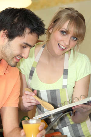 Young man and young smiling while reading cookbook photo