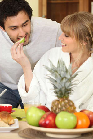 Young couple eating fruit at breakfast photo