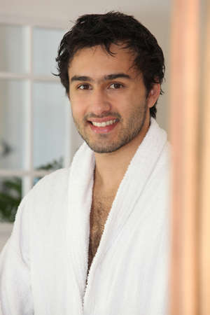 Smiling  young man in a bathrobe photo