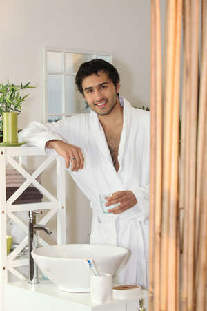 Man drinking a glass of water in his bathroom Stock Photo - 13988139