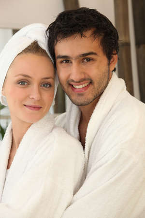 all smiles: portrait of young couple all smiles wearing bathrobe