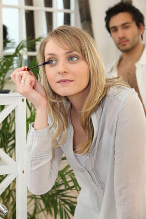 centralize: Blond woman applying makeup