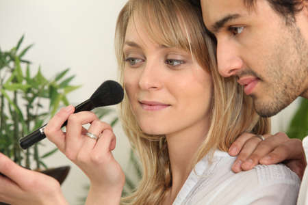 Man watching his girlfriend applying her make-up photo