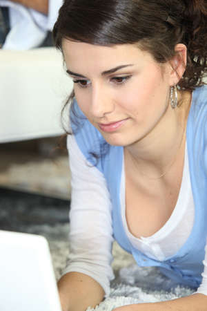 Young woman using a laptop lying on a rug photo