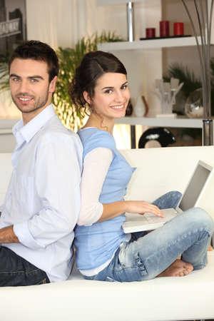 Couple back to back on white sofa photo