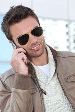 presumptuous: Trendy man with leather jacket on cellphone