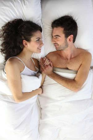 woman bed: Pareja acostada en la cama