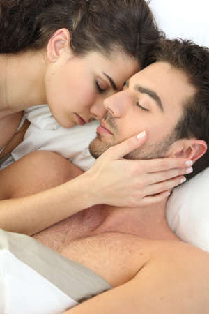 Young couple laid in bed together photo
