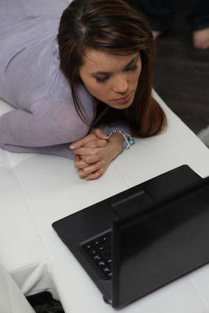 offset view: young woman lying and laptop