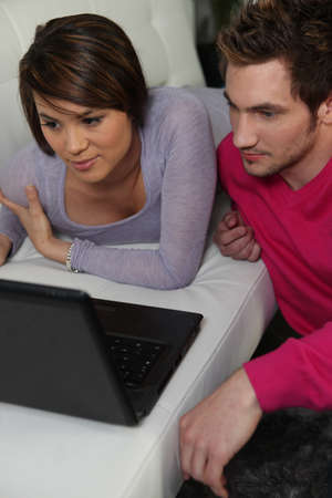 Young woman and young man in front of laptop Stock Photo - 13967199