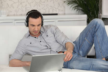 Man lying on a sofa with his laptop and a pair of headphones photo