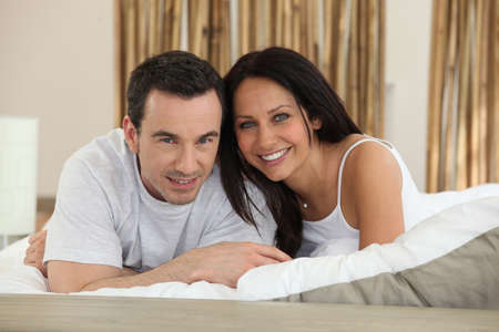 Young couple in love laying in bed photo