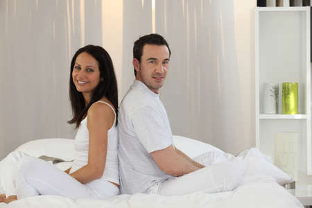 Couple sitting on a bed photo