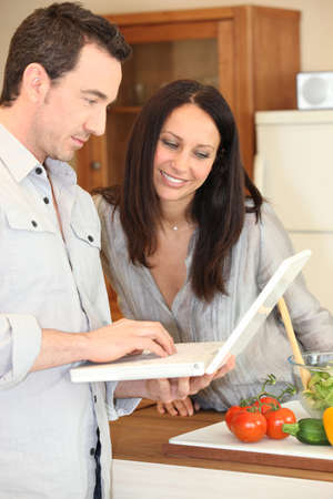 Couple using a laptop in the kitchen photo