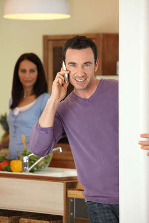 Man making a call whilst wife prepares meal photo