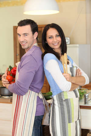 back kitchen: Couple stood back to back in kitchen Stock Photo