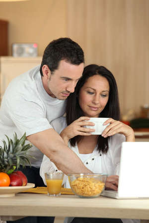 Couple eating breakfast in front of laptop photo