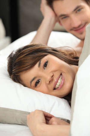 Happy young couple laying in bed Stock Photo - 14019810