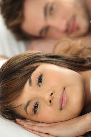 Couple happily laying in bed together photo