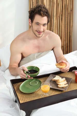 Young man having breakfast in bed photo