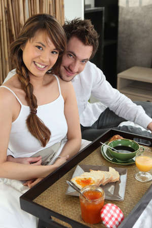 Couple with breakfast in bed photo