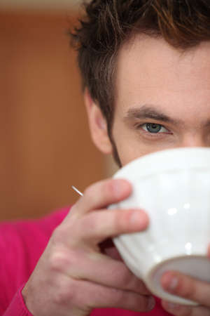 breakfasting: young man drinking warm beverage out of bowl