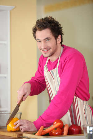 Young man chopping a bell pepper Stock Photo - 14022373