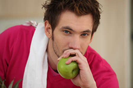 acidity: Man about to eat an apple