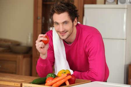 Man in kitchen holding tomato Stock Photo - 14014726