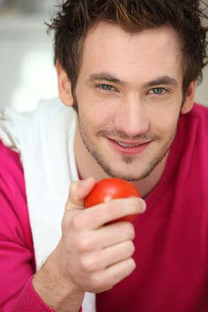 bushy: Portrait of a man holding a tomato Stock Photo