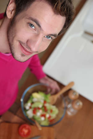 Young man making salad in the kitchen photo