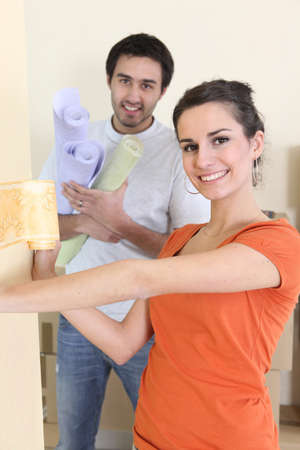 Couple wallpapering together photo