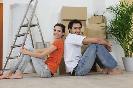 Couple sitting back to back next to step ladder photo