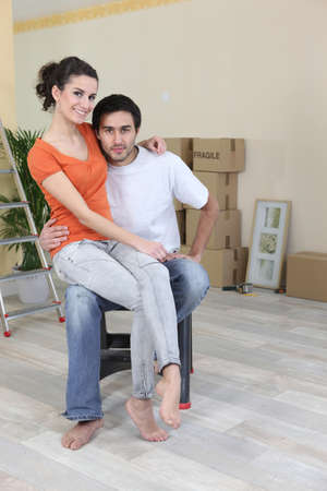 unpacked: Couple sat by unpacked boxes Stock Photo