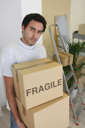 Young man carrying cardboard boxes on moving day photo