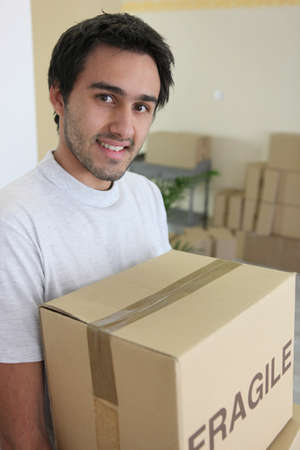 Man carrying a cardboard box on moving day photo