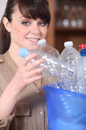 jeune femme de tri des bouteilles en plastique