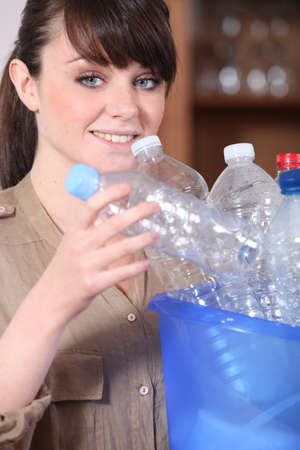 young woman sorting plastic bottles photo