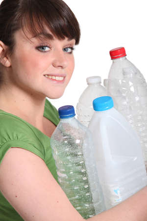 Young woman taking out bottles for recycling photo