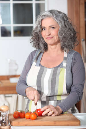 Portrait of a senior woman cooking Stock Photo - 14028742